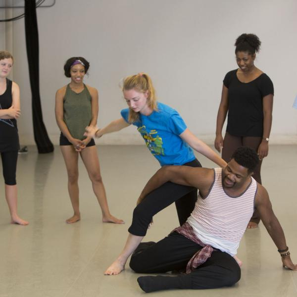 four students watch as a man and woman dance in a practice space