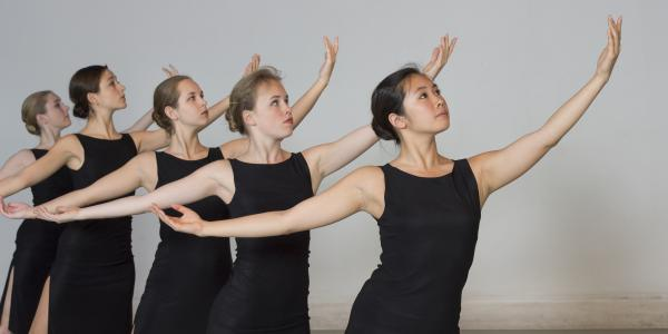 a line of five women in black dresses with arms held out in a ballet position