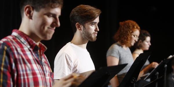 four students stand before a black curtain, reading from music stands